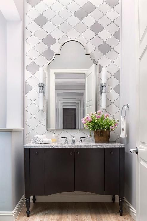 A silver arch mirror is mounted on white and gray arabesque backsplash tiles between two light nickel and white glass sconces fixed above a black footed washstand accented with a gray marble countertop finished with a sink and polished nickel faucet kit.
