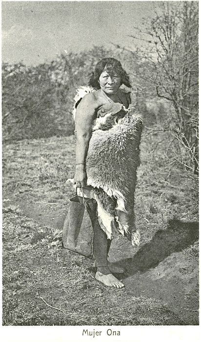 """""""Mujer Ona"""" Outdoor portrait of a Selk'nam woman, posed wrapped in a guanaco hide, holding a hide (?) container for water. Path, field, brush and woods in the background Culture/People: Selk'nam (Ona) Date created: circa 1930 Photographer: Father Alberto Maria De Agostini, 1893-1960"""