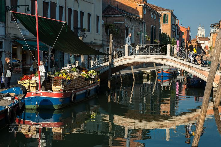 Floating greengrocer - Typical greengrocer in Venice. The boat with all the fresh fruits and vegetables arrives early morning near residential areas and all the sales take place by the canal.