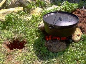 """Dakota Hole Cooking. The finished Dakota Hole is """"U"""" shaped and a fire is built in one side. The heat that is generated by the fire draws air into the other hole which begins a chimney effect and sustains the fire. Because the fire is below ground level, it is protected from windy weather and is more contained and thus safer."""