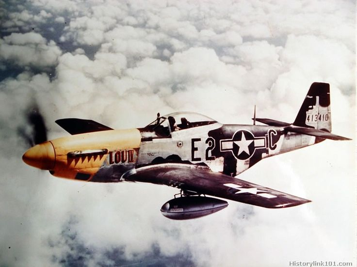 An 8th Air Force North American P-51D with auxiliary fuel tanks flies above the clouds over England.