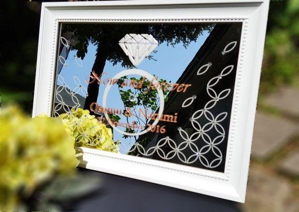 エレガントウェルカムミラー 結婚お祝いの記念品としても賜ります。デザインには、結婚を象徴するリングのデザインに、日本の吉祥伝統文様の「輪違い」という柄をアレンジしています。「輪違い:輪が限りなく連なって良い縁、良い出来事が続きますように」真ん中には「two become one」二人が一人になる・・・というメッセージを一緒に刻んでいます。文字、柄はミラーの表と裏に彫刻します。お二人のお名前、日付けを刻みこみます。フレームと、文字の書体は選べません。サイズ●36.4㎝×25.6㎝×2㎝※フレームは白の木製です。スタンド式です。※壁に取り付けるためのフックも備品としておつけします。作者からのメッセージ:パーティーのために作るウェルカムボードですが、最終的には自宅に持ち帰り飾ることになります。自宅に持ち帰ったとき洋風でも和風でも住まいになじむデザインの記念の品を創りたいと思いました。気にいっていただけたら嬉しいです。「two become…
