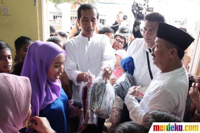 Gubernur DKI Jakarta Joko Widodo memberikan bantuan berupa perlengkapan sekolah, seragam serta sembako saat mengunjungi korban banjir di wilayah Ulujami, Pesanggrahan, Jakarta, Jumat (9/8).