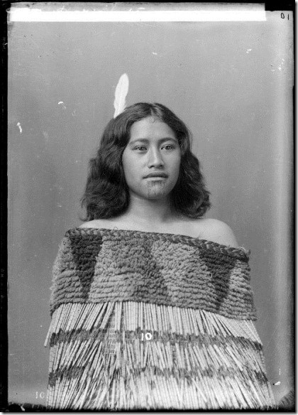 Portrait of Harimate, a Maori girl, with moko, wearing a cloak and with a white feather in her shoulder-length hair. Photograph taken by William Henry Thomas Partington, circa 1900, probably in the Wanganui region.