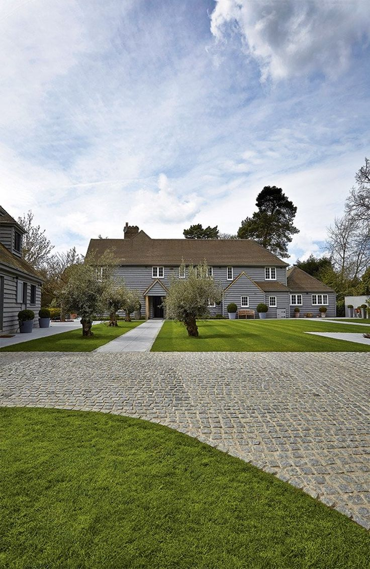 Incredible grey timber clad barn style house. Lovely level lush green lawn and stone paving.