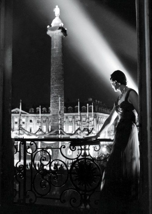 The Paris Ritz's Vintage - a guest looks out on the illuminated Place Vendôme at night from a room in the Ritz, 1950