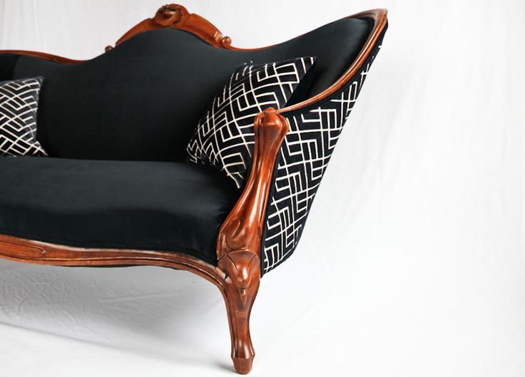An antique Victorian sofa circa 1890, reupholstered in a dark navy velvet from Herman Miller. The reverse side has been reupholstered in a navy patterned fabric. The throw pillows have visible gold zippers and match the contrasting front and back of the sofa. The hand carved frame has been fully restored to its original finish.