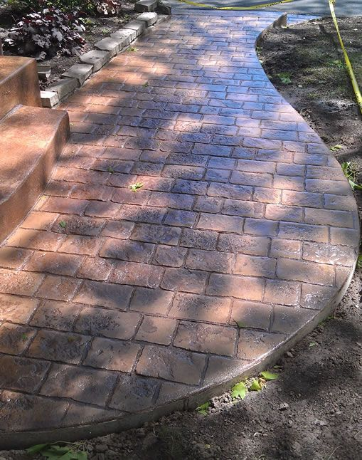 concrete walkway path with bricks stamped. much cheaper and easier that laying stone!