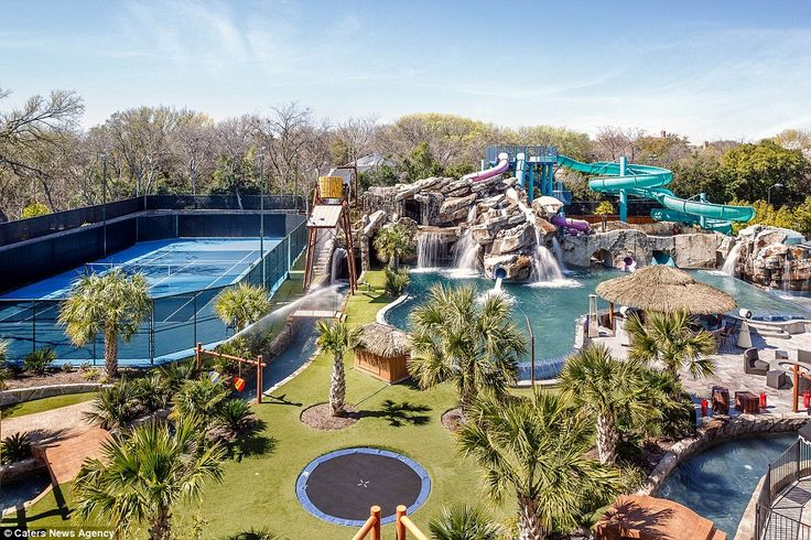 The incredible full scale water park provides a surprising contrast to the palatial home's classic exterior. Pictured, along with the three water slides and enormous pool, is a tennis court and built-in trampoline
