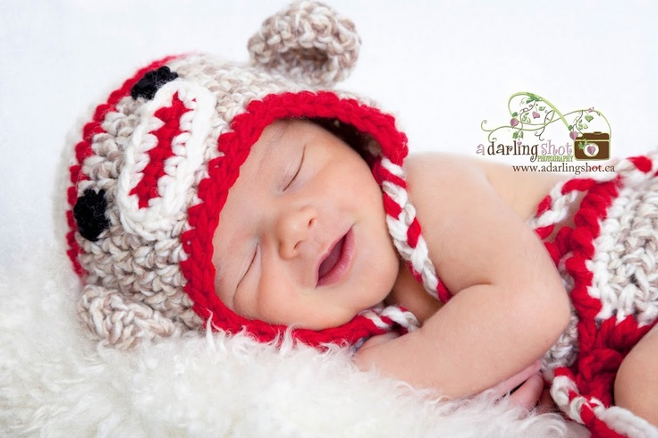 I love sock monkeys! And check out that newborn smile!