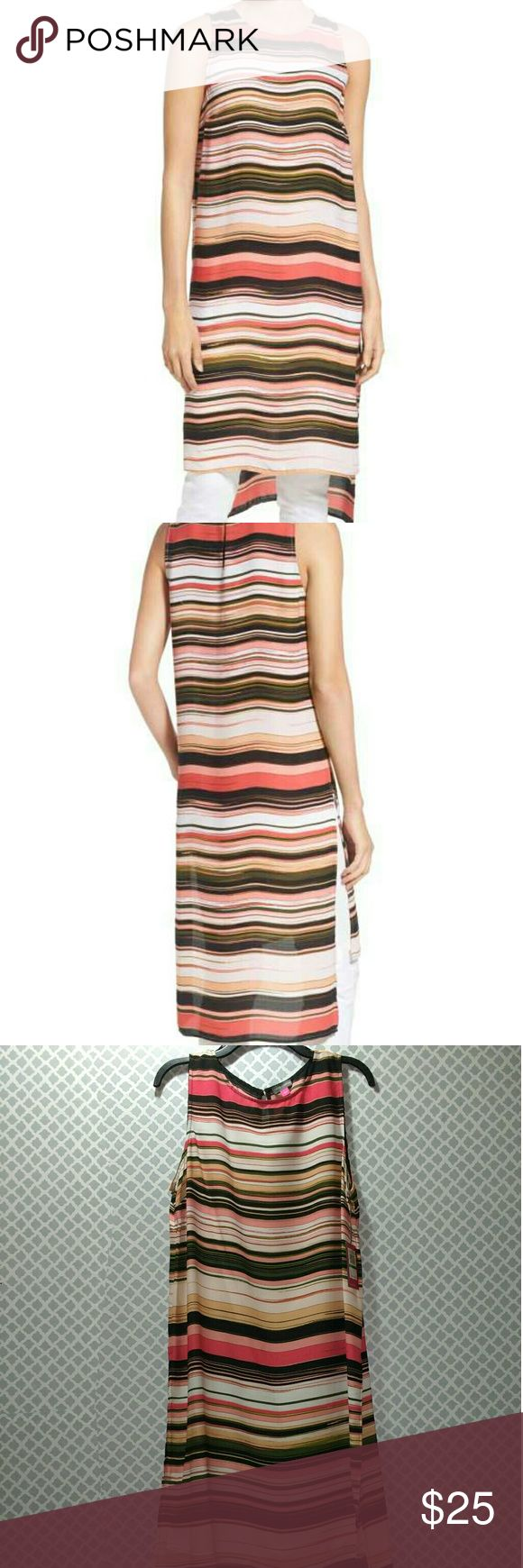 NWT Vince Camuto Long High/Low Stripe Tunic *** has small hole from security tag shown in last 2 pictures***  ** New with tags**  Beach-chic style comes to the streets via a sleeveless tunic flaunting a medley of variegated stripes in a warm- or cool-tone palette. The lightweight crepe style features an extra-long cut with a breezy high/low hem with deep side slits.  Back button-loop keyhole closure. Crewneck. Sleeveless. Side slits. Unlined. 100% polyester. Machine wash cold, tumble dry…