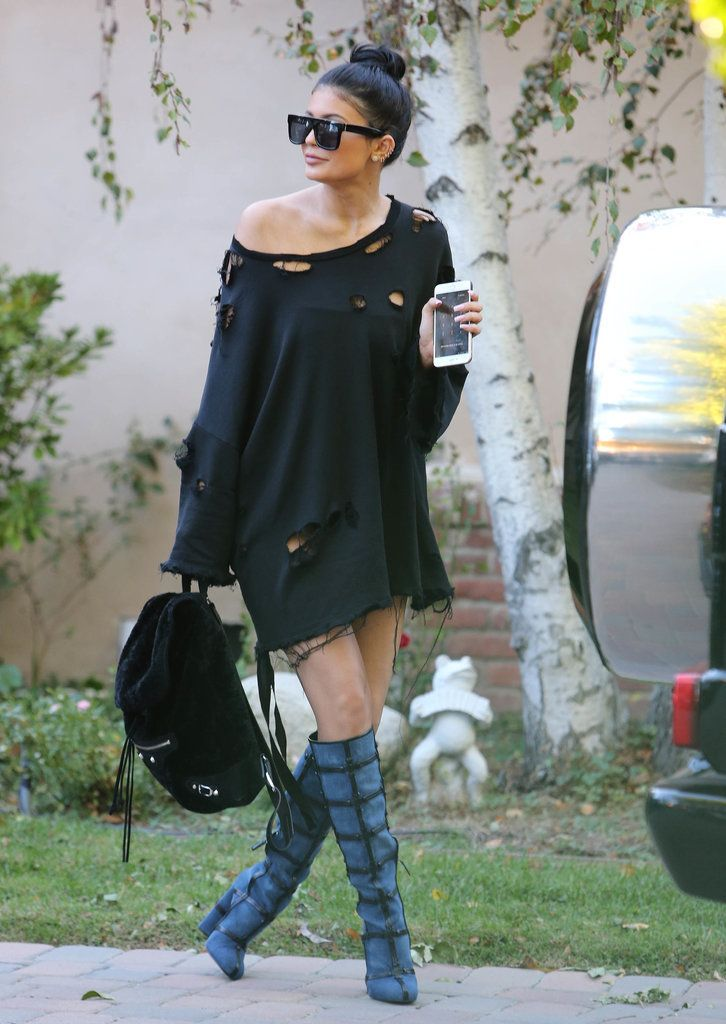 Kylie Jenner paired her oversized and distressed sweater with knee-high boots and a backpack.