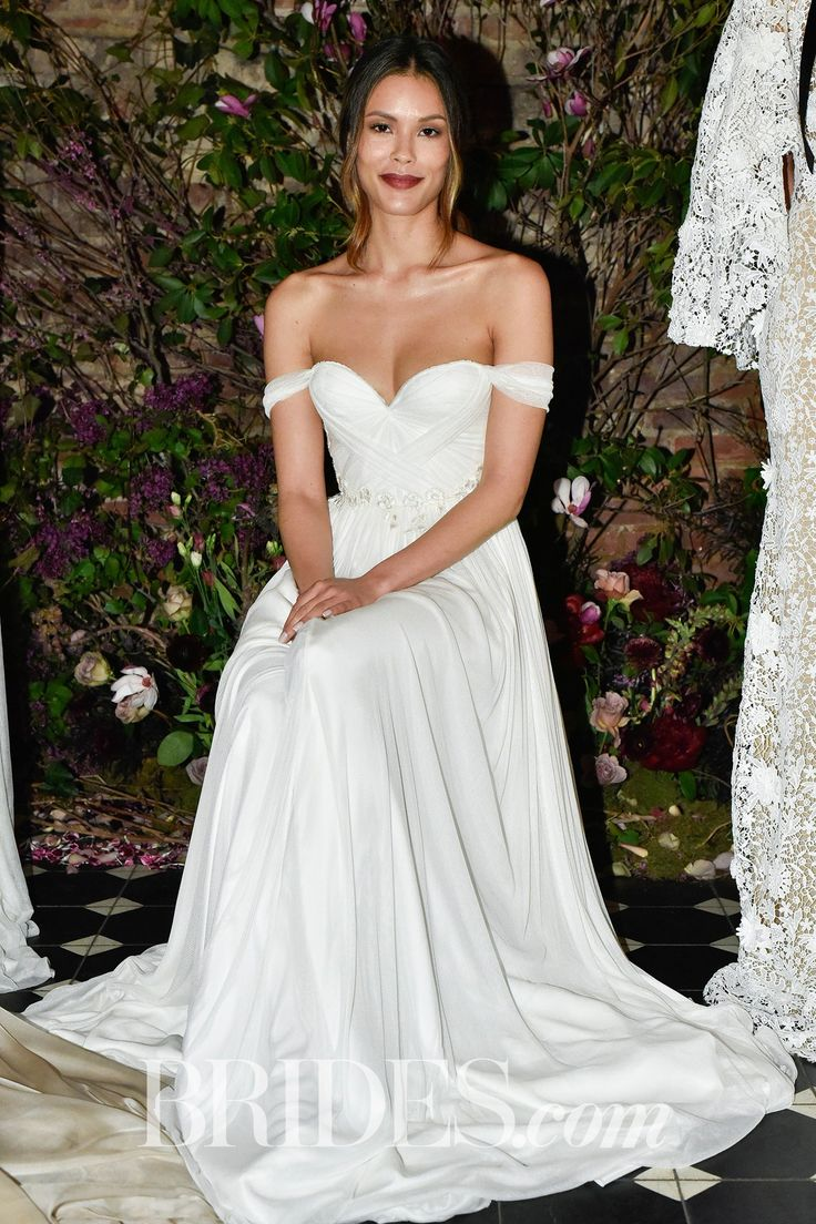 "This wedding dress from Sarah Seven's ""The Romantics Part II"" spring bridal collection features off-the-shoulder sleeves with a sweetheart neckline, and empire waist skirt."