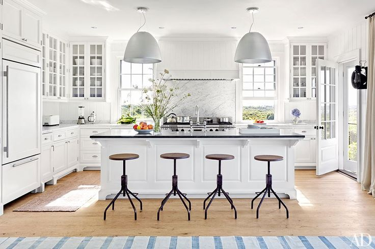 The kitchen features Artemide pendant lights, a Sub-Zero refrigerator, a Wolf range, and stools from Robert Stilin.