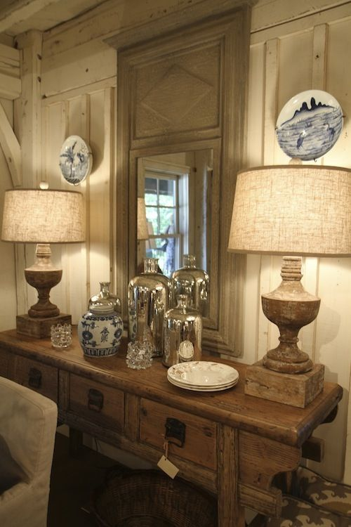 Pretty vignette-wonderful wood architecture, table, French mirror, lamps, accessories with blue accents.