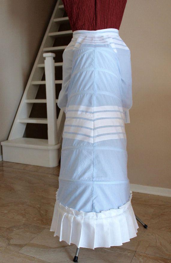 Bustle Vittoriano per sostegno a gonne del 1875 circa. Realizzato in cotone azzurro con righe bianche e decorato con una balza in cotone bianco . La