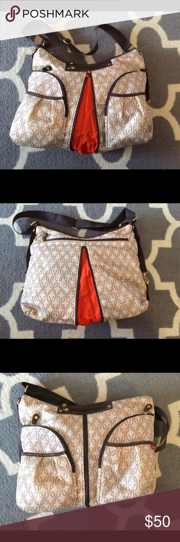Skip Hop Versa Diaper Bag/Purse Large purse-style diaper bag.  Small zip phone pocket on front, 2 zip & 2 open pockets on front, 4 open pouch pockets inside. Changing pad inside back zip pocket (never used).  Center zip opens/closes to adjust size.  Some staining on left side of back (may come out in wash, just saw it), otherwise brand new condition. Bought for a formal event & carried once.  Sold at Nordstroms & Skip Hop online. Skip Hop Bags Baby Bags