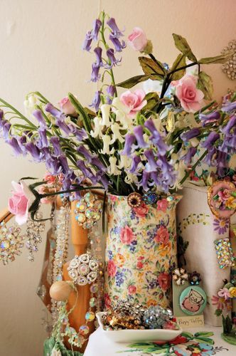 Old-fashioned flowers, bluebells and pink roses, in cheery floral pitcher.