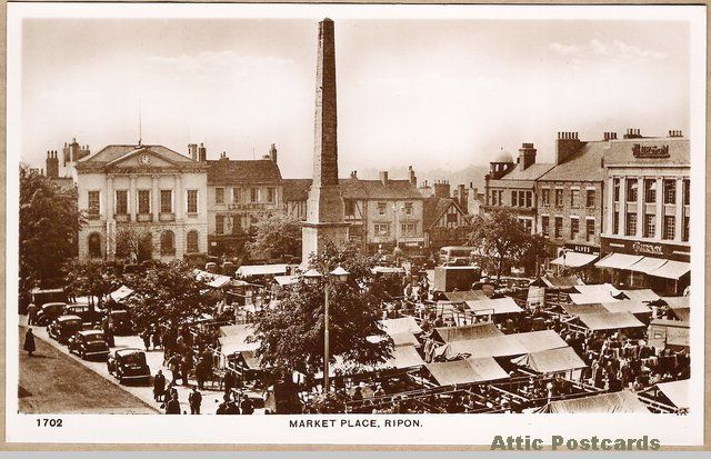 Vintage real photo postcard of the Market Place in Ripon, Yorkshire, England. Shows many stalls, old cars and people.