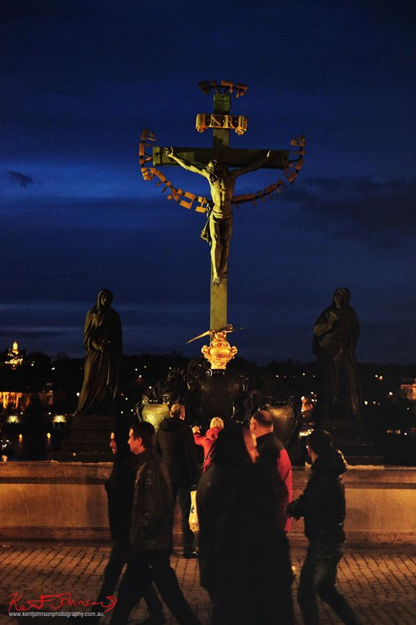 Woman rubbing the bronze of a statue of Jesus on the cross at night. The Charles Bridge in Spring Prague by Travel and Lifestyle Photographer Kent Johnson.