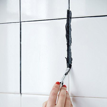 Believe it or not you can paint over grout. If you don't want to go through the hassle of removing and placing grout, or ripping off and installing new tiles, a bit of acrylic craft paint can go a long way towards giving a bathroom a new look. In this case, black paint was applied over the grout to provide a contrast with plain white tiles. After painting, apply a grout sealer to seal the paint.