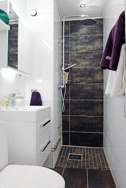 Contraste de tonos negros en pared y suelo con mobiliario y sanitarios en blancos para un cuarto de baño reducido