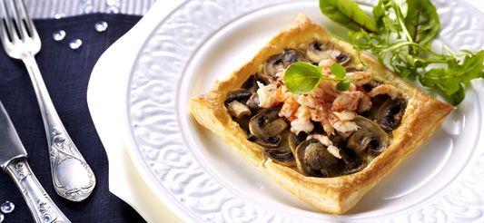 (bovenstaande ingrediënten zijn voor 6 personen)      Verwarm de oven voor op th. 6 – 180°C en neem er het rooster uit.     Snij de champignons in fijne plakjes en bak ze aan in de olijfolie en het citroensap. Dek af, laat 5 min. op zacht vuur stoven, verwijder het deksel en laat het vrijgekomen vocht grotendeels verdampen (niet helemaal) Voeg peper en zout toe.     Prak de kaas met een vork om 'm zachter te maken. Laat de deegvierkantjes op het bakpapier van de...
