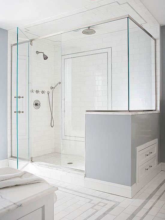 The tile inset from the bathroom floor is repeated on the shower wall and ceiling. The two person shower is outfitted with wall-mount, handheld, and rain-style showerheads. Every inch in this remodel works hard, including the drawers added under the shower bench for extra storage./