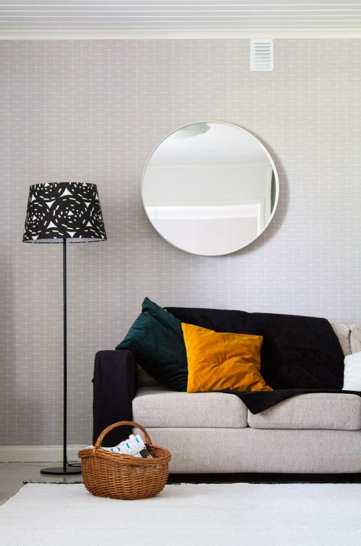 Olohuone, valkoinen räsymatto, pyöreä peili, harmaa tapetti. Living room, white rag rug, round mirror, gray wallpaper.