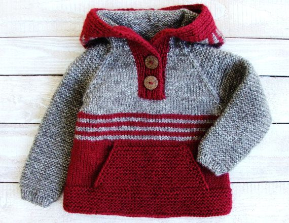 This sweater will fit baby girls up to 2 years old.  Hand knitted from soft bulky easy care acrylic yarn, with coconut shell buttons, large front pocket, and cozy, over-sized hood.  Sweater measures 14 from shoulder to hem, 12 across chest, and 14 from neckline to cuff.  Machine washable.