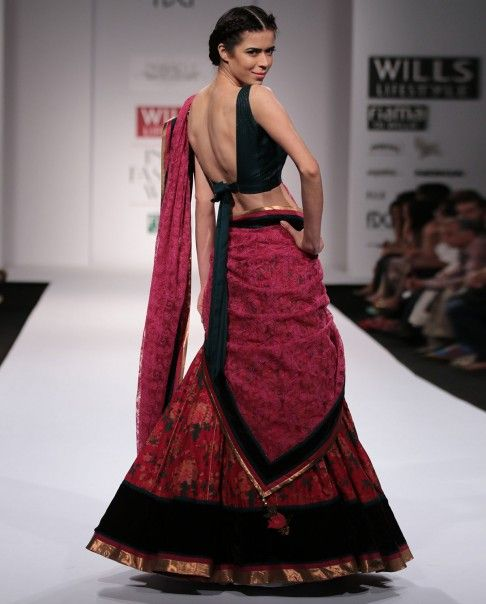 Red floral printed kalidar lengha with velvet border. The set also includes bottle green sleeveless blouse and red net dupatta. Wash care: Dry clean onlyDisclaimer: There might be a slight color variation in this item as this image is from the actual runway show.