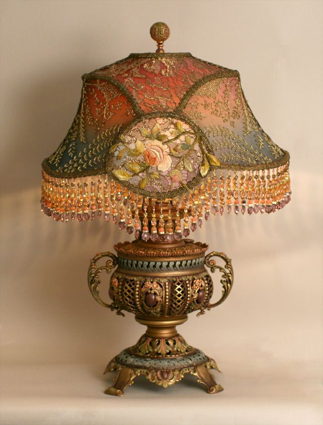 A hand-painted, highly detailed converted antique oil lamp base holds a hand-dyed silk lampshade dyed from mauve to dusty blue and covered in a collection of ornate antique textiles. The front panels are covered in a rich warm gold lace and the oval panels are then overlaid with appliques taken from a French textile. The sides are covered in an opulent antique beaded net. Hand beaded fringe in matching tones - lights up beautifully.