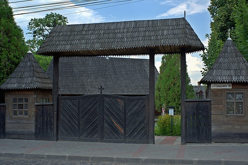 """Street Entrance Gate of St. Nicholas Wooden Church in Sahaidachnoho Str.  Located in Chernivtsi, Ukraine. Built around 1607 in canonical """"village house"""" style and geometry. Burnt almost down in 1992, and restored and reopened in 1996.  Tags:      Chernivtsi      Ukraine      2012      building      clouds      church      sanctified      spiritual      architecture  sky  evening  historical place  Eastern Orthdox  village house style  ancient  17th century  wooden architecture"""