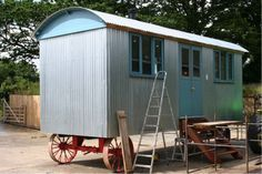 A really large sized shepherds hut, galvanised steel roof and sides with painted end boards and hardwood windows and doors.