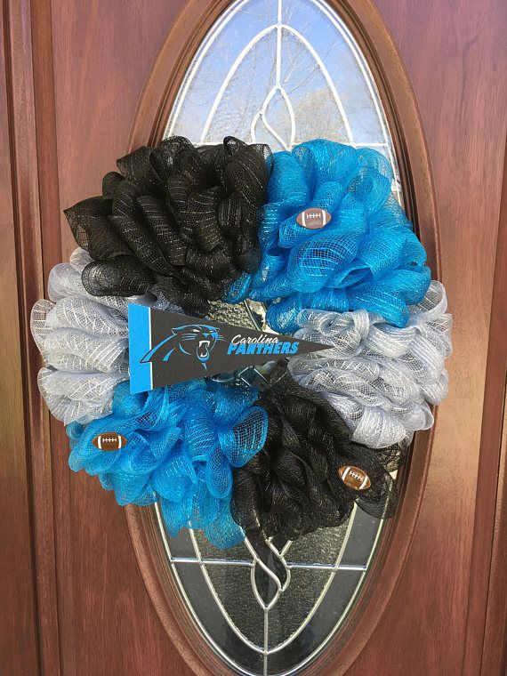 Carolina Panthers wreath. This wreath is made with Carolina Panther blue, black and silver deco mesh to match their team colors. There are 3 football embellishments throughout and a Carolina Panthers pennant in the middle. This is the perfect one of a kind wreath for any die hard Panther fan!   Measurements are 21 in diameter and 5 1/2 deep. This wreath can be used either indoor or outdoor. *If buying multiple items your shipping rate will be adjusted