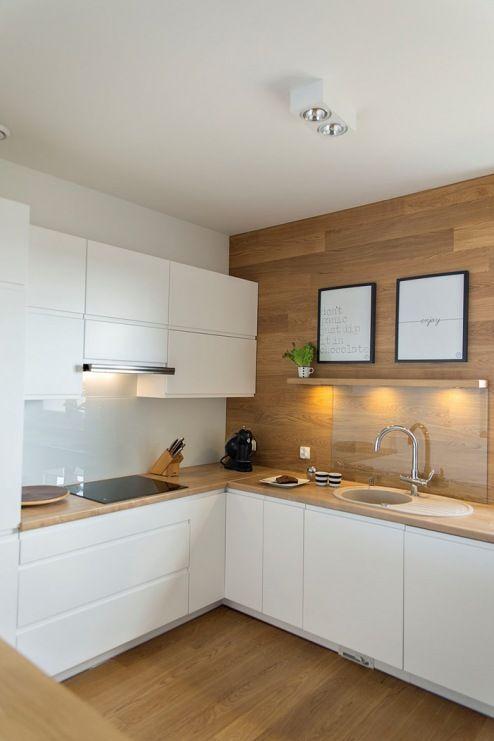 Biała kuchnia została wzbogacona o drewniane elementy, które idealnie…