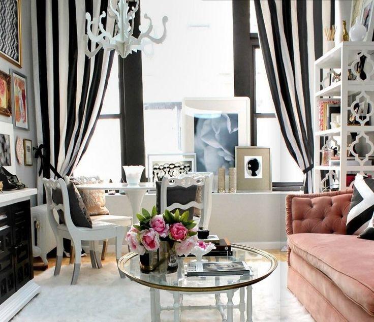 salon blanc et noir décoré de rideaux rayés et canapé corail comme accent