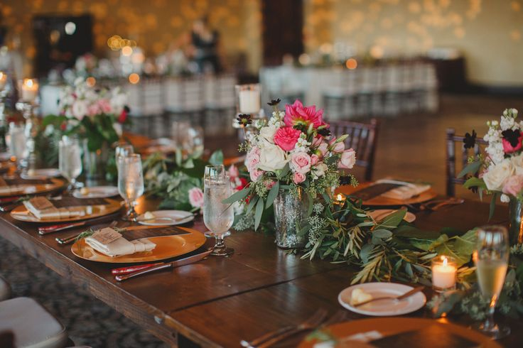 a varnished wood farm table for the wedding party was dressed with garland and highlighted by bridesmaids' bouquets in mercury glass vases.