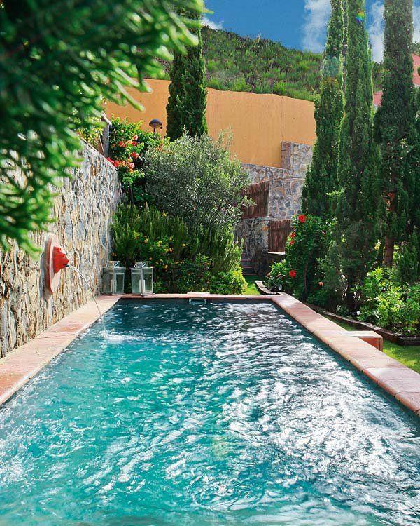 Un hueco para la piscina Su diseño a modo de alberca, tan característico de los patios andaluces, es perfecto cuando el espacio es reducido y se busca rapidez en la ejecución, ya que no necesita que se excave el terreno. Bordeada de baldosas de barro, la cubeta se pintó en un color gris que, con la luminosidad mediterránea, intensifica el azul del agua. Al fondo, arriates de cipreses, arbustos y plantas de flor, enmarcados por traviesas de madera, sombrean este bucólico rincón del jardín.