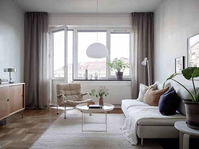 modele de salon gris et blanc, avec canapé gris clair, parquet marron clair, table basse ronde, chaise longue gris taupe, rideaux couleur lin style scandinave couleur taupe clair