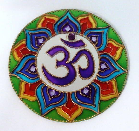 Mandala em espelho de 15cm de diâmetro, pintura vitral, decorado com pedrinhas acrílicas e tinta relevo dourada. <br> <br>Mandala em sânscrito significa círculo. <br>São veículos para o religamento da nossa consciência com o Todo Universal, do qual fazemos parte. <br>As Mandalas além de decorativas servem para imprimir energias e trazer beleza ao ambiente em que se encontram. <br> <br>Om (?) é o mantra mais importante do hinduísmo e outras religiões. Diz-se que ele contém o conhecimento dos…