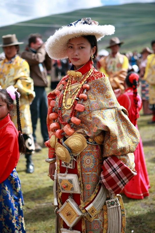 Litang Horse Festival, Tibet. Beautiful woman from the Litang area in traditional clothing. She wears a chuba and sheepskin hat, multiple huge and heavy prayer boxes and linking chains popular in Kham, and a spectacular necklace with enormous pieces of coral (this alone is probably worth tens of thousands of dollars).