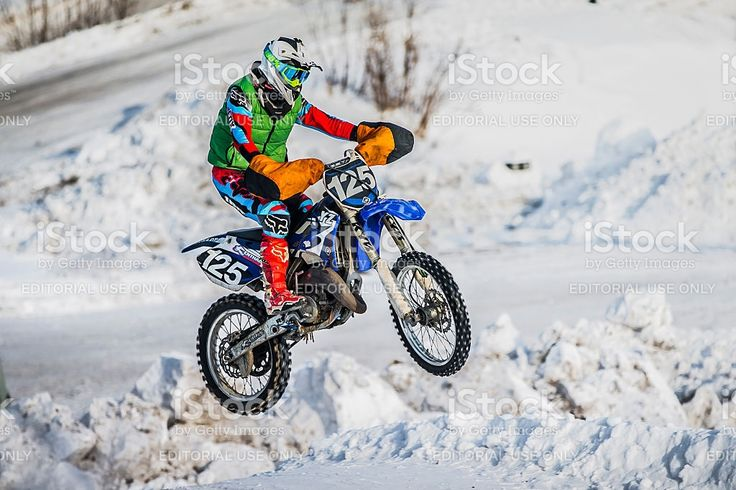 Kopeysk, Russia - January 23, 2016: jump racer on a motorbike over snowy hill during Cup Winter motocross