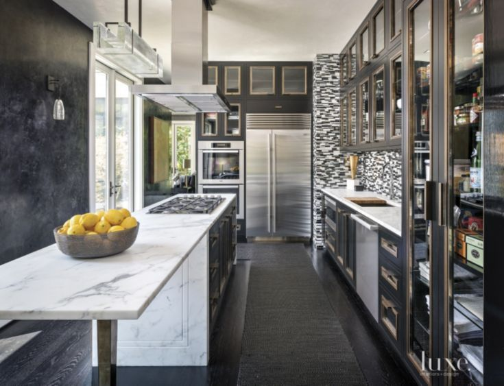 Lacquered cabinets from Seattle Cabinet & Design, featuring inlaid bronze-and-nickel trim by Metal Solutions and marble countertops from architectural Stone Werkes, coordinate with a custom Ann Sacks backsplash in this contemporary kitchen. #LuxeTurns10