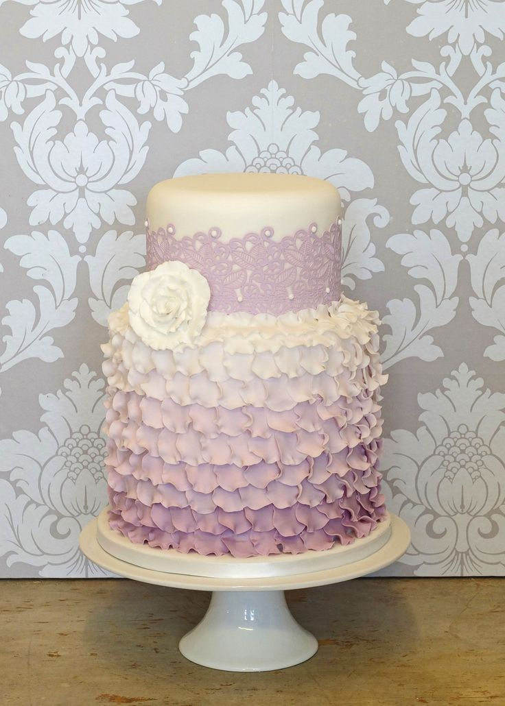 "A dainty, romantic little cake featuring two of the hottest wedding trends - frilly ombré ruffles and intricate sugar lace. A large ruffled rose and piped dots finish the look.  This cake could be adapted to fit in with any wedding colour scheme.  As seen: 6"" and 8"" tiers."