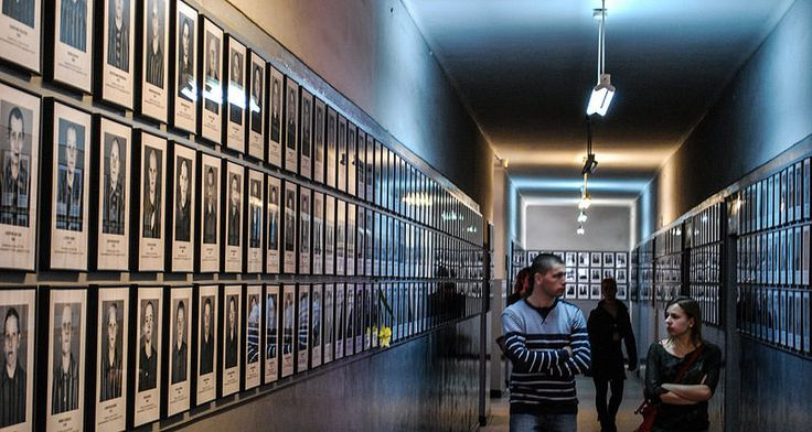 Auschwitz I. Block 6 - main exhibition. Visitors surrounded by registration photographs of the prisoners...