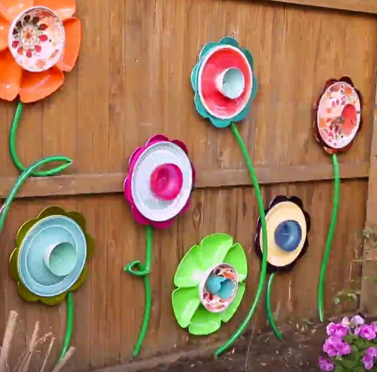 HGTV Idea - garden fence decor from plastic plates and old hoses
