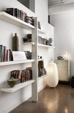 bachelor loft - contemporary - Home Office - Other Metro - stephane chamardThe shelving unit is an Ikea hack. Many people love the clean good looks of the company's Lack shelf. But it's difficult to display anything besides lightweight accessories on it due to its limited load-bearing capacity. Chamard solved the problem and made the Lacks bookworthy by installing a single vertical support and staggering the shelves off it.