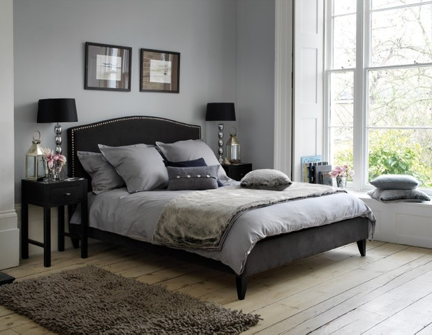 Grey bedroom with black bed with stud detail
