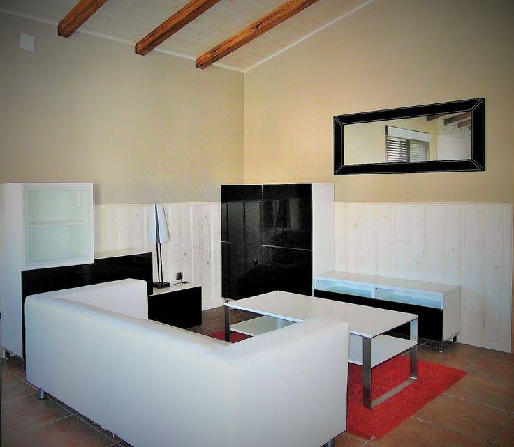 salon de casa de hormigon acabado zocalo de madera y pared lisa pintada